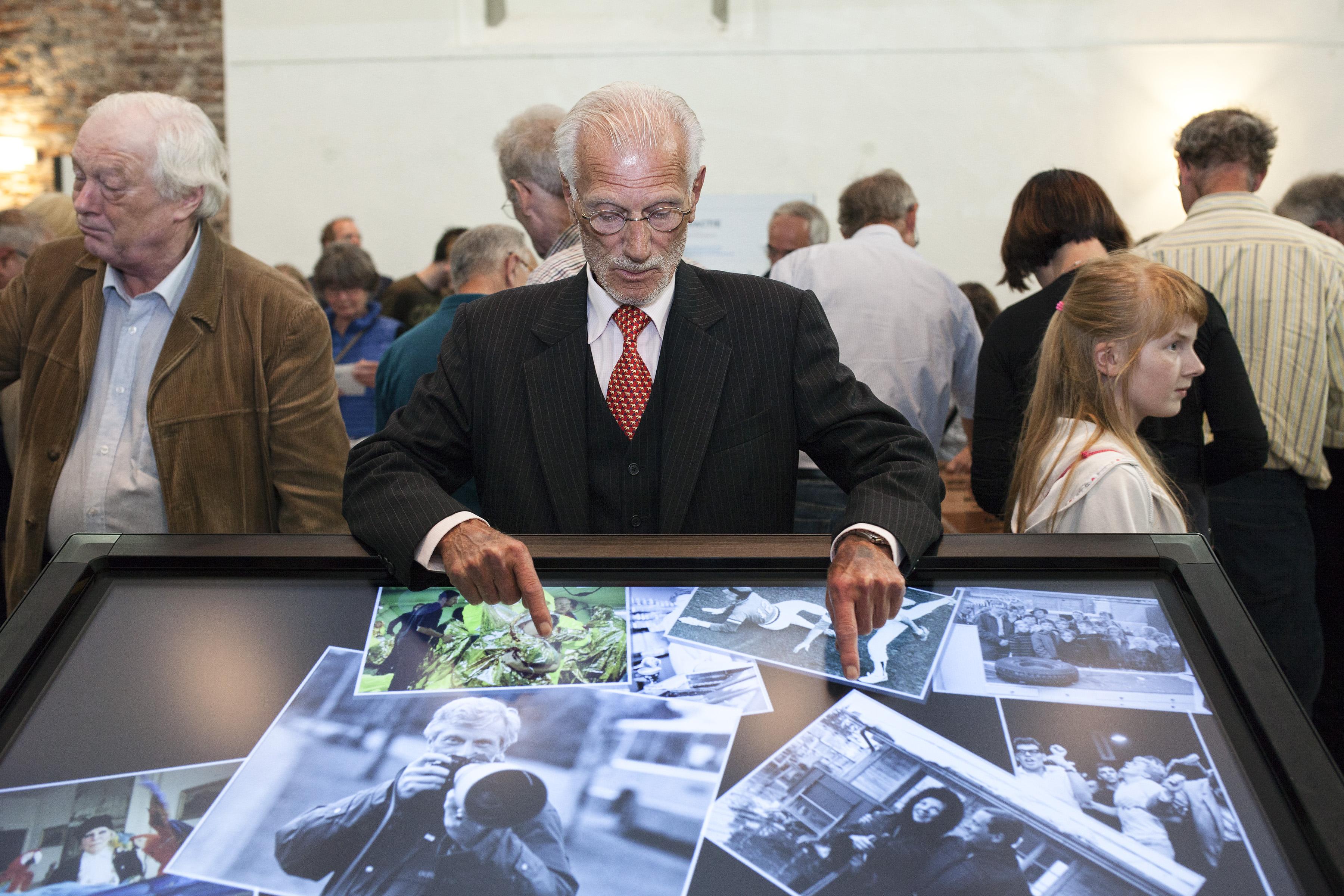 Haarlem, 9-7-2016: Poppe de Boer achter de viewer op zijn tentoonstelling in het Noordhollands archief. Rechts staat een kleindochter van De Boer. foto: UnitedPhotos / Remco van der Kruis